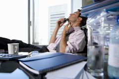 Young businessman shaving at desk in office by book, mug and glass on desk (differential focus) Stock Photos