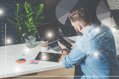 Young businessman in shirt sits in office at table and uses smartphone.On desk is laptop,tablet computer,cup of coffee. Stock Images