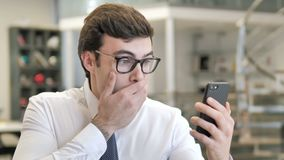 Young businessman in shock while using smartphone stock footage