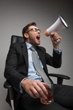 Young businessman shouting and sitting on chair. Stock Photos