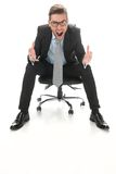 Young businessman shouting and sitting on a chair. Stock Photography