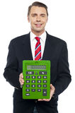 Young businessman showing big green calculator Royalty Free Stock Image