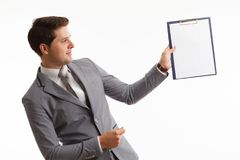 Young businessman showing blank clipboard, isolated on white background. Success in business, job and education concept shot Stock Photography