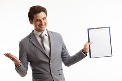 Young businessman showing blank clipboard, isolated on white background. Success in business, job and education concept shot Stock Image
