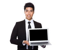 Young Businessman showing the blank screen of laptop computer Stock Photos