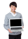 Young businessman showing the blank screen of notebook computer Royalty Free Stock Images