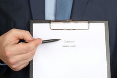 Young businessman showing contract  by pen Stock Photos