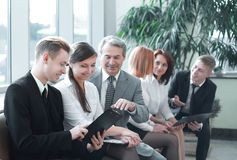 Young businessman showing a document to his colleagues. Office weekdays royalty free stock photos