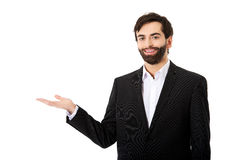 Young businessman showing empty copyspace on hand. Royalty Free Stock Photos
