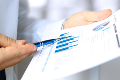 The young businessman showing graphs by pen Stock Photography