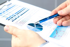 The young businessman showing graphs by pen Stock Image