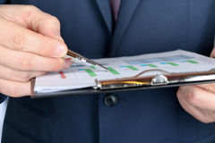 Young businessman showing graphs by pen Stock Photography