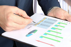 Young businessman showing graphs by pen Stock Image