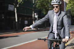 Young businessman showing hand sign while riding bicycle Royalty Free Stock Image