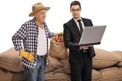 Young businessman showing something on a laptop to a farmer Royalty Free Stock Photography