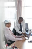 Young businessman showing something to male colleague on laptop at office desk Stock Photos