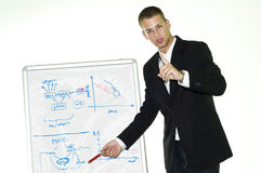 Young businessman showing something on white board. Young businessman in black suit showing something on white board Stock Photo