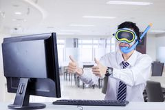 Young businessman with diving equipment in office. Young businessman showing thumbs up at the monitor while wearing diving equipment the office Stock Image