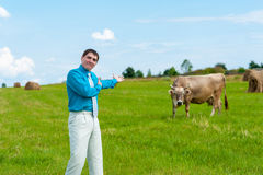Young businessman shows a good cow Stock Photo