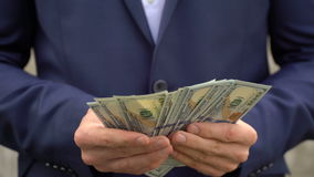 Young businessman shows his money close-up.