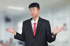 Young businessman shrugging shoulders against stock photo