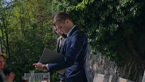 Young businessman signed a contract. Zooming-in footage of a young businessman singing the contract an passing to the young partner to singed outdoors on sunny stock video footage