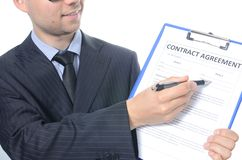 Young businessman signing a contract. Isolated on white Royalty Free Stock Photos