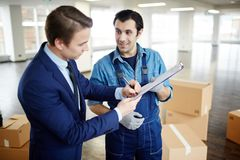 Work is done. Young businessman signing document held by load worker after carrying out his work Stock Photos