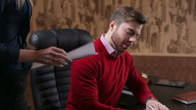 Young businessman signing a document hold by his female secretary. Bearded businessman working in office with his assistant stock footage