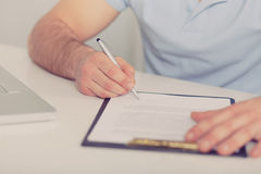 Young businessman signs a contract, toned Royalty Free Stock Photos