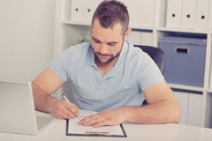 Young businessman signs a contract, toned Royalty Free Stock Images