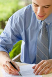 Young  businessman signs document Royalty Free Stock Photography