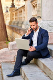 Young businessman siting on the stairs with his laptop and talki Royalty Free Stock Photography