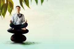 Young Businessman Siting on Zen Rock with Yoga Meditation postur Royalty Free Stock Photo