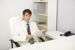 Young businessman sits in the study Royalty Free Stock Image