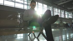 Young businessman sitting at airport and using smartphone with sun flare at background. Close up portrait of handsome. Business man in sunglasses with smart stock footage