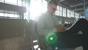 Young businessman sitting at airport and using smartphone with sun flare at background. Close up portrait of handsome. Business man in sunglasses with smart stock video footage