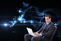 Young businessman sitting on an armchair working with a laptop Stock Photo