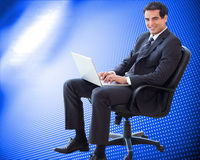 Young businessman sitting on an armchair working with a laptop Royalty Free Stock Photos