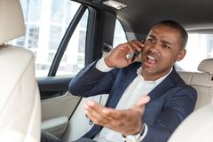 Young businessman sitting on back seat in car talking on smartphone shouting at driver irritated royalty free stock photography