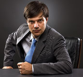Young businessman sitting behind the desk. Businessman sitting behind his desk looking at the camera on gray Royalty Free Stock Images