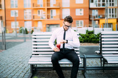 Young businessman sitting on the bench outdoors and looking on wrist watch while drinck coffee. Young businessman sitting on the bench outdoors and looking on Stock Photos