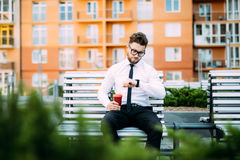 Young businessman sitting on the bench outdoors and looking on wrist watch while drinck coffee. Young businessman sitting on the bench outdoors and looking on Stock Photo