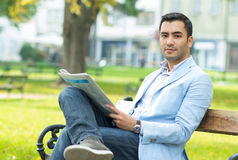 Young businessman sitting on bench and reading newspaper. Outdoor - outside Stock Photo
