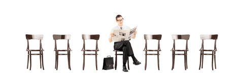 Young businessman sitting on a bench and reading a newspaper whi Stock Image