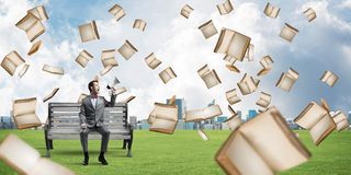 Businessman in summer park announcing something in loudspeaker and books falling from above. Young businessman sitting on bench and screaming emotionally in Royalty Free Stock Image