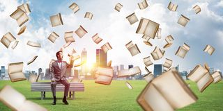 Businessman in summer park announcing something in loudspeaker and books falling from above. Young businessman sitting on bench and screaming emotionally in stock photography