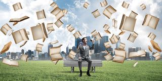 Businessman in summer park announcing something in loudspeaker and books falling from above. Young businessman sitting on bench and screaming emotionally in Stock Images