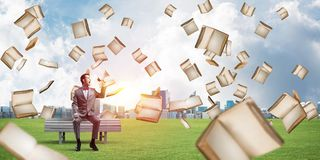 Businessman in summer park announcing something in loudspeaker and books falling from above. Young businessman sitting on bench and screaming emotionally in royalty free stock photo