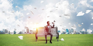 Businessman in summer park announcing something in loudspeaker and paper planes flying around. Young businessman sitting on bench and screaming emotionally in Royalty Free Stock Photography